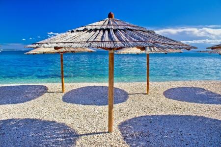 Pebble beach and turquoise sea umbrella, Zrce beach, Island of Pag, Croatia Standard-Bild
