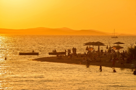 People on the beach silhouettes at golden sunset in Zadar, Croatia photo