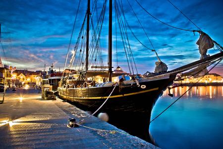 Old wooden boat in Vodice harbor, night view, Dalmatia, Croatia