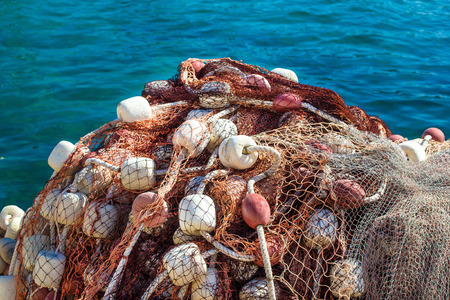 Fishing net pile by the blue sea photo