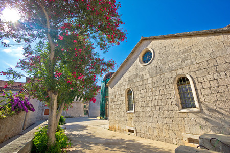 starigrad: Stone church and flowers of Hvar island, town of Stari Grad, Croatia