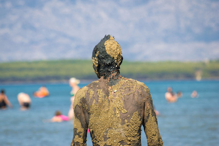 anonymus: Unrecognizable person in healthy mud on beach back portret view