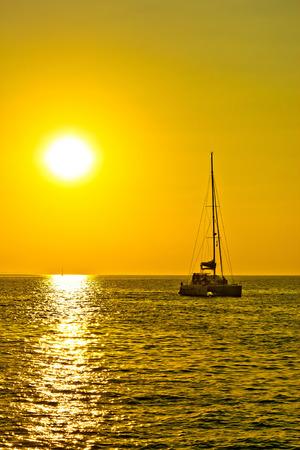 Katamaran Segelboot auf goldenen Sonnenuntergang auf offenem Meer vertikal