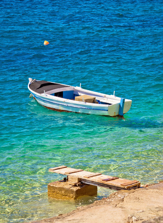 Old wooden fishermen boat on turquoise beach, Mediterranean sea
