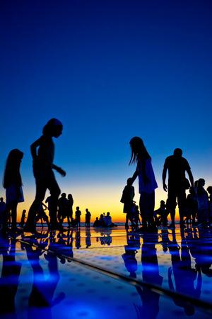 People silhouette on colorful sunset, Zadar, Croatia Standard-Bild