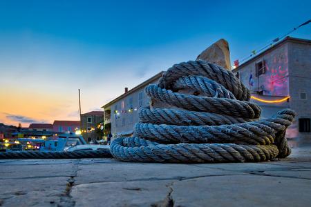 mooring bollard: Wound boat rope on mooring bollard evening view, mediterranean village