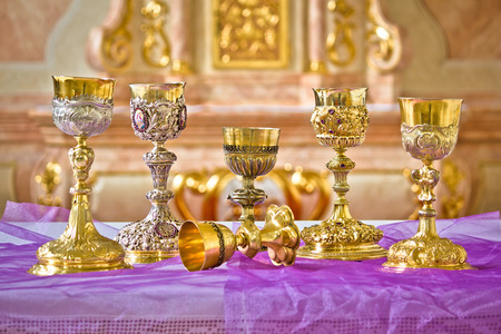 religious service: Golden holy grails on church altar view, religious equipment