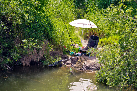 Fishing spot and gear in green landscape, chair and fishing rod by tje river