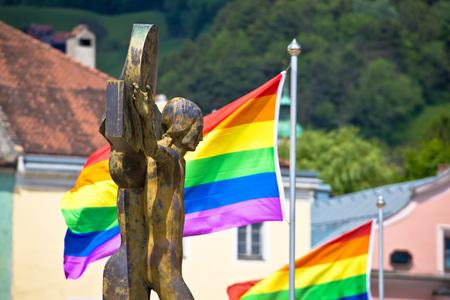 transexual: Crucifixión de Jesucristo y vista de banderas de orgullo gay, Innsbruck, Tirol, Austria