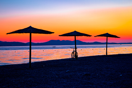 Beach and parasols on colorful sunset view, Adriatic sea, Zadar, Dalmatia region of Croatia
