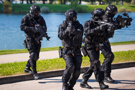 Special forces tactical team of four in action, unmarked and unrecognizable swat team