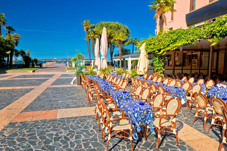 Cafe and walkway on Garda lake in town of Sirmione, Lombardy region of Italy