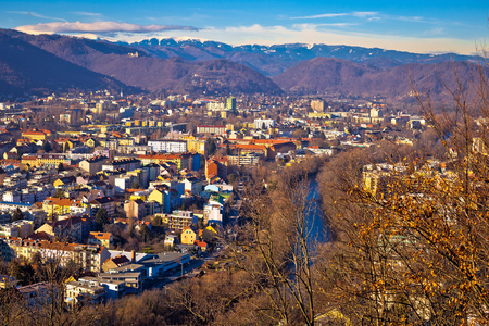 Graz and Mur river aerial cityscape view, mountains under snow backgroung, Styria region of Austria