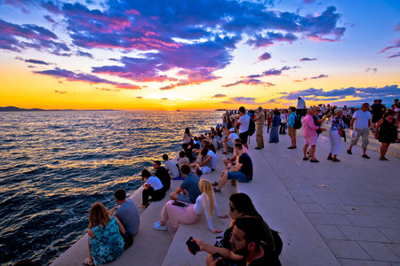 ZADAR, CROATIA - July 18 2017:  Unidentified people on Zadar sea organs at sunset. Many tourists visits unique architectural object located on Zadar waterfront - musical instrument powered by the sea streams. Редакционное