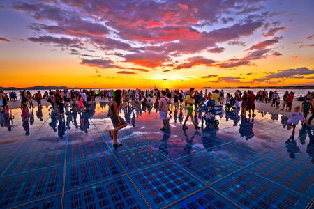 ZADAR, KROATIEN - 18. Juli 2017: Nicht identifizierte Leute in der Stadt von Zadar-Grüßen zum Sonnenmarkstein in der Region von Dalmatien, Kroatien bei buntem Sonnenuntergang. Viele Touristen besuchen diese solarbetriebene Anlage an der Seeküste. Standard-Bild - 94783687