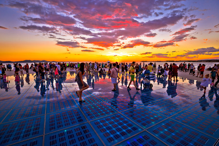 ZADAR, CROATIA - July 18 2017:  Unidentified people in city of Zadar Greetings to the sun landmark in region of Dalmatia, Croatia at colorful sunset. Many tourists visits this solar powered installationon sea coast.