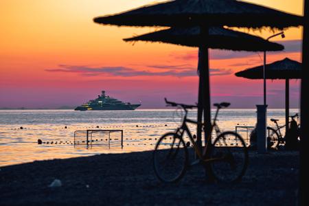 Beach and parasols on colorful sunset with large yacht view, Adriatic sea, Zadar, Dalmatia region of Croatia Stock Photo - 120220155
