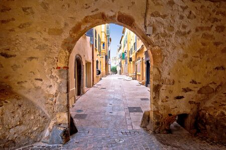 Saint Tropez historic town gate and colorful street view, tourist destination of French riviera