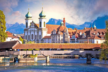 Luzern wooden river Bridge and church view, landmarks in town in central Switzerland