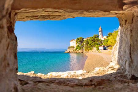 Monastery on pebble beach in Bol view through stone window, island of Brac, Dalmatia, Croatia