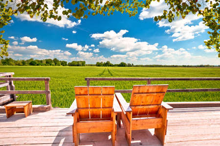 Relax deck chairs in agricultural landscape. Green wheat field under blue sky view, Podravina region of northern Croatia
