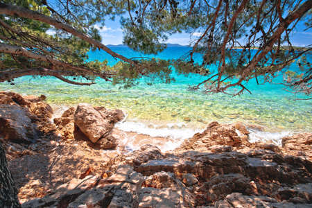 Idyllic turquoise beach view through pine tree in Zadar riviera, Pakostane in Dalmatia region of Croatia