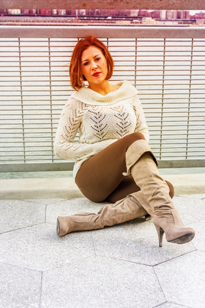 Young American Woman wearing white knit sweater, brown pants, long boots, sitting by railing beside river, sad,  thinking.