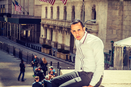 Young American Businessman traveling, working in New York, wearing white shirt, black pants,  sitting outside vintage office building on street to take work break. Filtered effect. Stok Fotoğraf