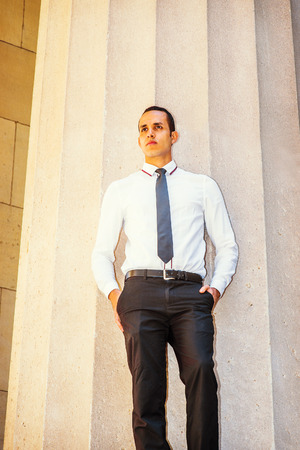 lost in thought: Young American Businessman wearing white shirt, black tie, hands in pockets, standing outside office building in New York, thinking, lost in thought. Stock Photo