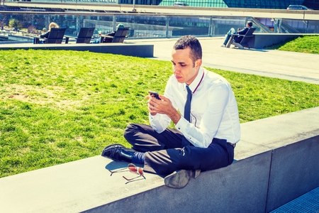 sitting on the ground: American Businessman traveling, working in New York, wearing white shirt, black pants, leather shoes, sunglasses on ground, sitting on street park, reading message on mobile phone. Filtered effect