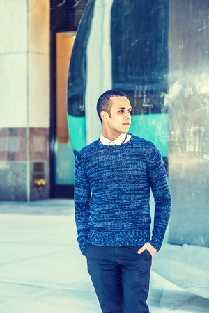 collarless: Young American Man wearing blue patterned knit sweater, black pants, two hands putting in pockets, standing by metal mirror in New York, looking away.