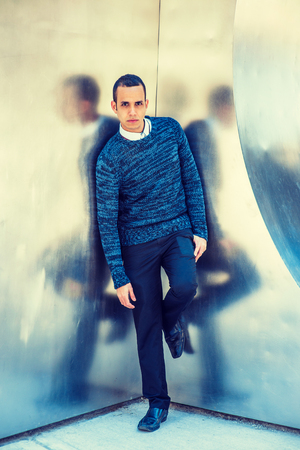 Young American Man wearing blue patterned knit sweater, black pants, leather shoe, standing by silver wall with reflections in New York.