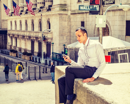 Young Businessman traveling, working in New York, wearing white shirt, black pants, sitting outside vintage office building, texting on cell phone. Wall Street sign on background. Filtered effect Imagens