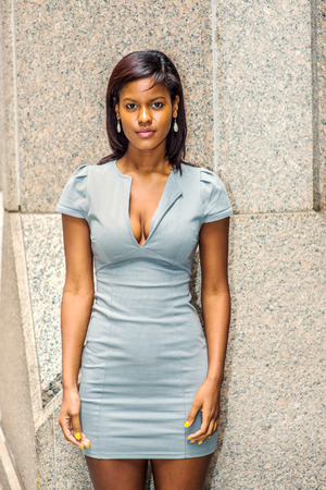 Portrait of Young African American Businesswoman in New York, wearing gray business fit dress, drop earrings, standing against column outside office building, greeting you. Stock Photo
