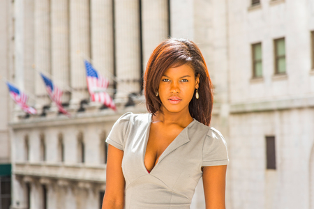 Young African American Businesswoman traveling, working in New York, wearing gray business dress, drop earrings, standing outside vintage office building, looking forward. USA flags in background.