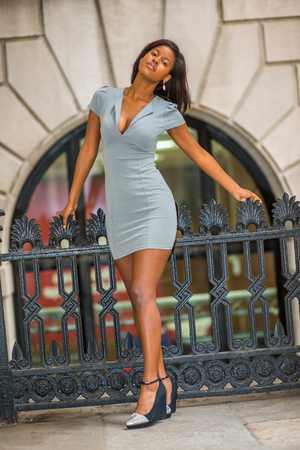 African American Businesswoman Fashion in New York, dressing in gray business dress, wedge pumps, tilting head, stretching body, standing on balcony outside office building to take work break.