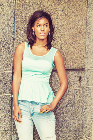 Lonely Girl. Young pretty black woman wearing green tank top, fashionable jeans, drop earrings, standing against marble wall in New York, sad, thinking, lost in thought. Woman Casual Street Fashion. Stock Photo