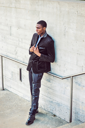 Young African American Man wearing black fashionable jacket, pants, leather shoes, standing against wall on street in New York, hands on lapel, looking down, thinking, lost in thought. Street Fashion.