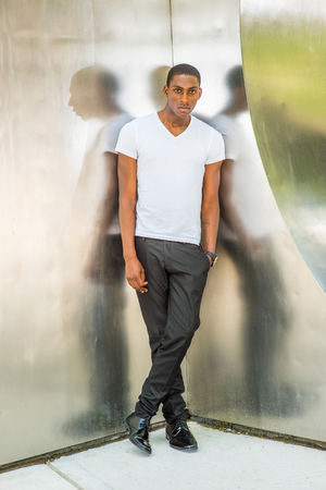 Street Fashion. Young African American Man wearing white V neck T shirt, black pants, leather shoes, hand in pocket, standing in corner of metal mirror walls in New York. Instagram filtered look Stock Photo
