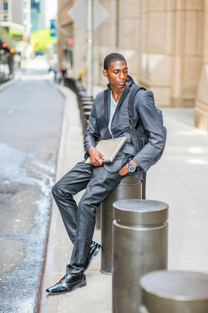 Young African American Man traveling, studying in New York,  carrying shoulder bag, holding laptop computer, sitting on pillar on vintage street, looking down, thinking.
