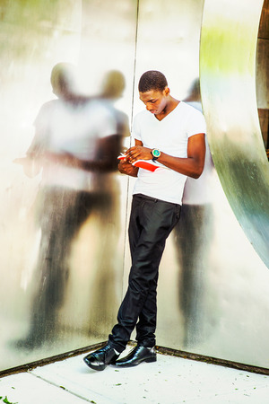 Young African American Man wearing white V neck T shirt, black pants, leather shoes, standing against  metal mirror walls, looking down, turning pages, reading red book. Instagram filtered look Stock Photo