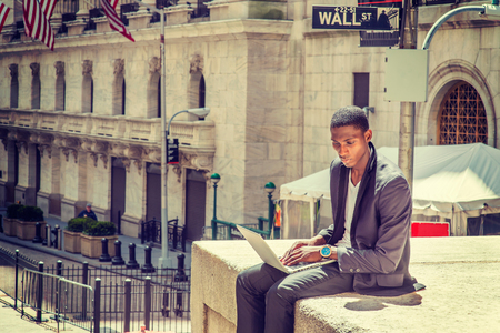 Young African American man traveling, working in New York, sitting on street by vintage office building, reading, working on laptop computer. Wall Street sign on background. Instagram filtered look