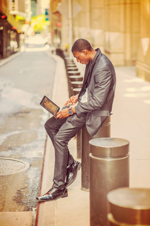 pantalones abajo: Young African American man traveling, working in New York. College student sitting on pillar on vintage street outside office building, reading, working on laptop computer.