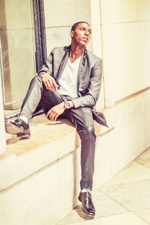 Young African American man wearing black fashionable jacket, white undershirt, black pants, leather shoes, sitting against window frame in New York, sad, emotionally looking up. Street Fashion. Stock Photo