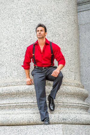 Handsome, strong, middle age businessman wearing long sleeve red shirt, trousers with suspenders, leather shoes, bending over,  standing against column outside in New York, relaxing, thinking.