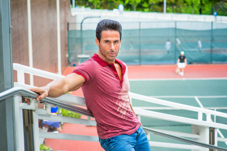 Man waiting for you. Wearing a red Polo shirt, blue jeans, stretching arms on the railing, a handsome, sexy, middle age guy is standing by a tennis court, passionately looking at you.