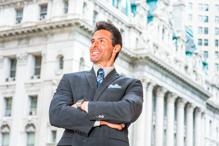 Businessman. Dressing in dark blue suit, necktie, wristwatch, crossing arms, a handsome, sexy, middle age businessman is standing in the front of an office building, confidently looking forward. Stock Photo