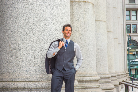 Man Waiting Outside. Dressing in light gray shirt, dark blue vest, necktie, jacket taken off on shoulder, handsome, middle age businessman is standing by columns outside office,  smiling, looking up. Stock Photo