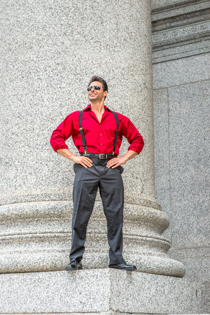 Handsome, strong, middle age businessman wearing long sleeve red shirt, trousers with suspenders, leather shoes, sunglasses, hands resting on hips, standing by column outside, smiling, relaxing,
