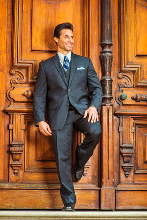 hopeful: Door to Success. Dressing in a dark blue three piece suit, patterned necktie,  a handsome, sexy, middle age businessman is standing by an old fashion style office door way, confidently looking up.